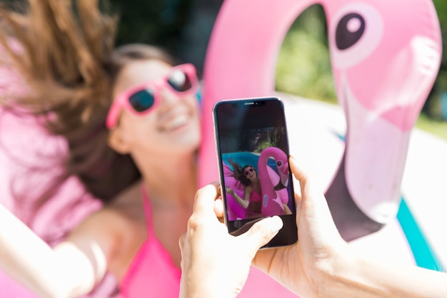Female photographing beautiful teen woman on inflatable flamingo