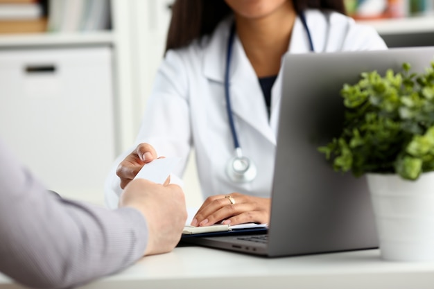 여성 의사는 클라이언트에 흰색 명함을 제공합니다