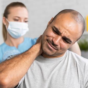 Женский физиотерапевт и мужчина с болью в шее