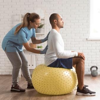 Женский физиотерапевт, проверяющий мужскую боль в спине