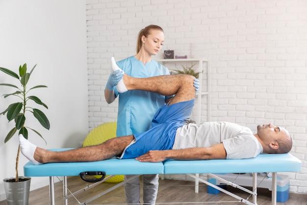 Female physiotherapistchecking man's leg mobility