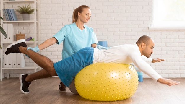 ボールの上で男性患者を助ける女性理学療法士