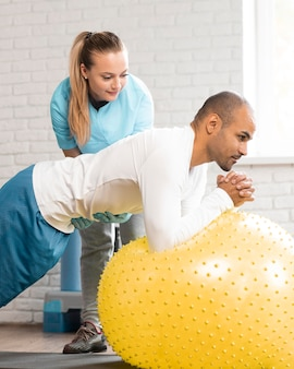Female physiotherapist helping male patient with ball exercises