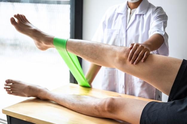 남성 환자의 부상당한 다리를 치료하는 여성 물리 치료사