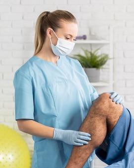 Женский физиотерапевт с пациентом мужского пола