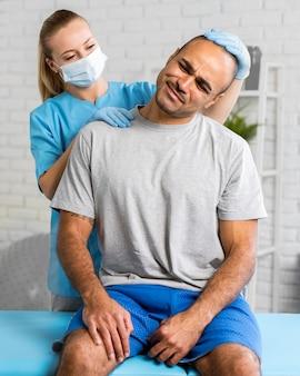 Женский физиотерапевт с медицинской маской проверяет боль в шее мужчины