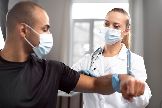 Female physiotherapist with medical mask and gloves checking man's elbow