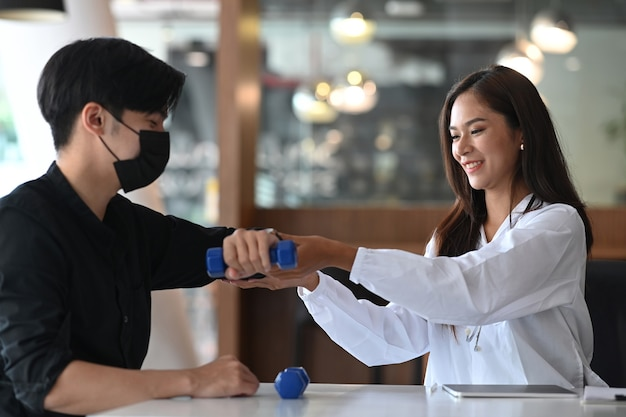 여성 물리치료사는 남성 환자의 부상당한 팔을 치료하는 검사를 하고 있습니다.