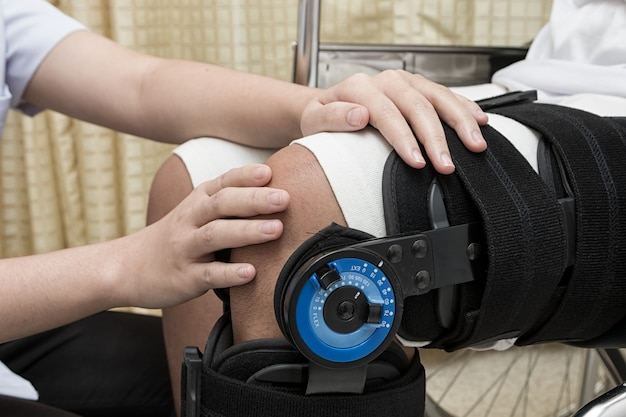 Female physiotherapy adjusting walking brace on patient's leg in wheel chair