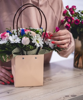 Female picking up bouquet of different flowers in paper gift bag with handles. vertical