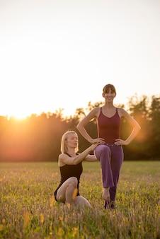 女性のピラティストレーナーは、夕方の太陽に照らされた美しい牧草地で屋外でエクササイズをしているときに、トレーニング生を修正します。