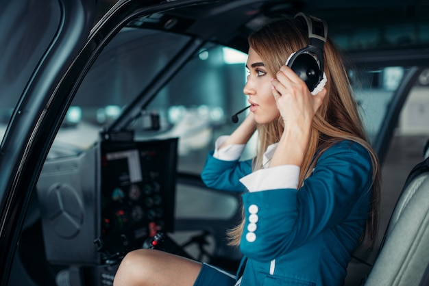Female pilot in headphones in helicopter cabin