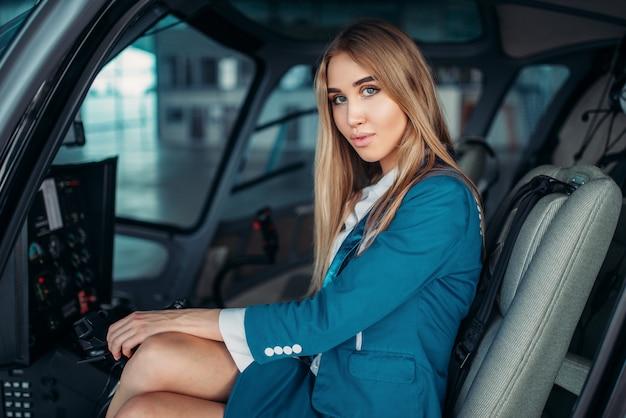 Женщина-пилот в наушниках в кабине вертолета