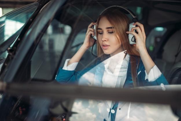 Женщина-пилот в вертолете, вид из лобового стекла