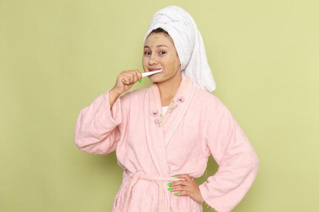 Female in pink bathrobe cleaning her teeth