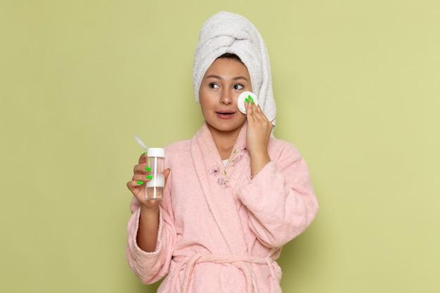 Femmina in accappatoio rosa che pulisce tutto il trucco dal suo viso