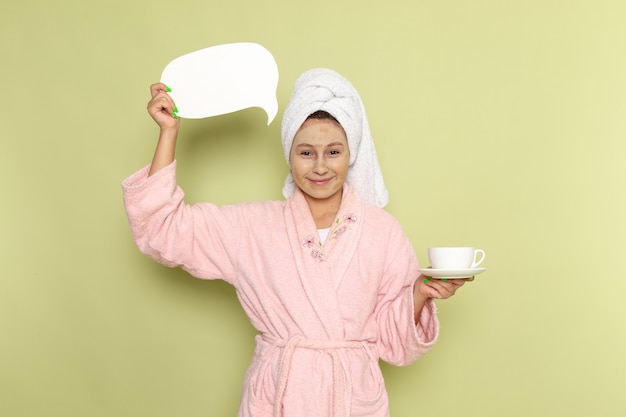 Female in pink bathrobe holding coffee cup