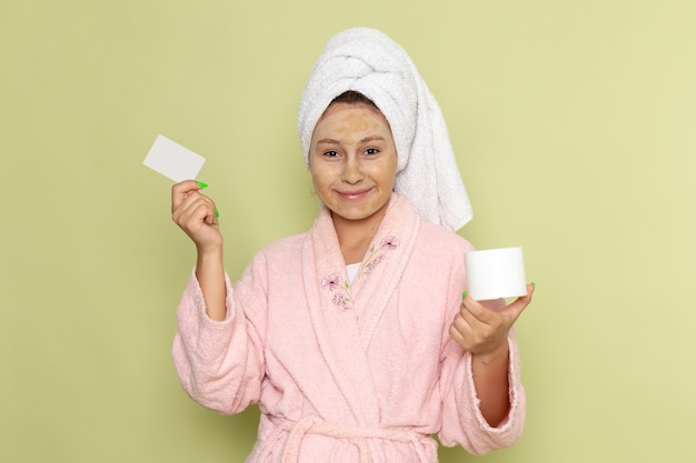 Female in pink bathrobe holding white card and cream