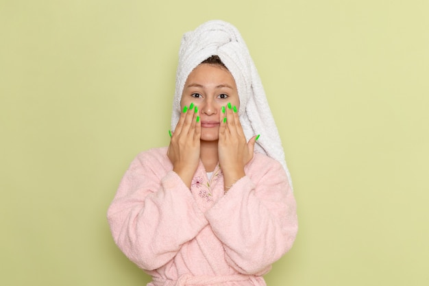 Female in pink bathrobe rubbing her face with cream
