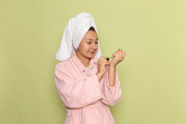 Femmina in accappatoio rosa sorridente e che fissa le sue unghie