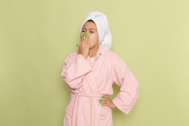 Female in pink bathrobe sneezing