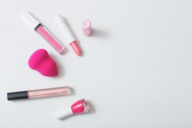 白い背景の上の女性のピンクの化粧品