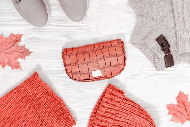 Женская розовая вязаная шапка, шарф, пуловер, кожаные сапоги, маленькая сумочка.
