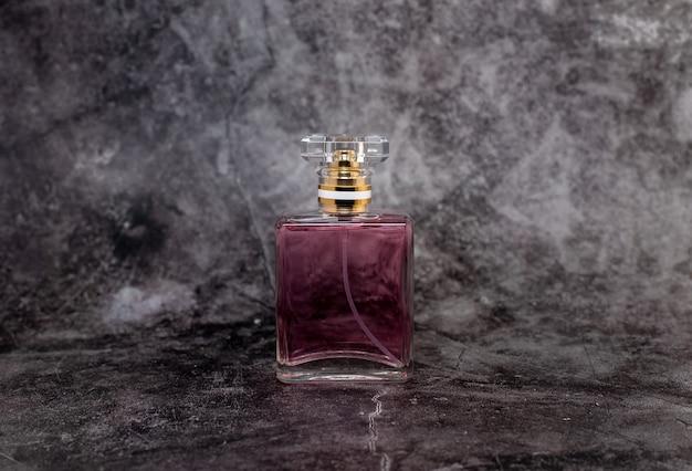 暗い背景の上の女性のピンクの香水