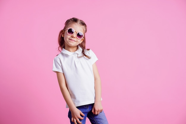 Female in pink round sunglasses isolated on pink