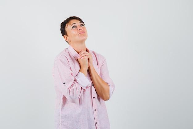 Donna in camicia rosa stringendo le mani nel gesto di preghiera e guardando impotente, vista frontale.
