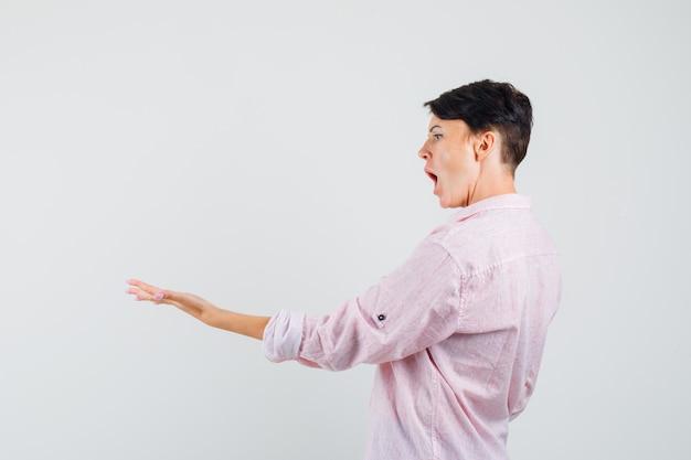 Donna in camicia rosa tendendo il palmo e guardando eccitato.