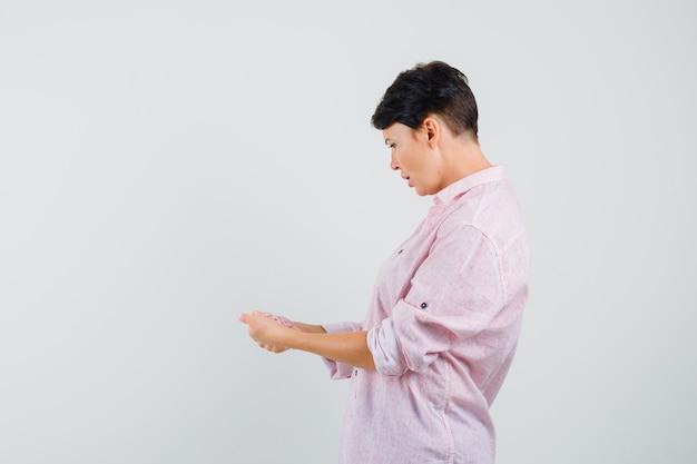 Donna in camicia rosa guardando qualcosa che fingeva di essere tenuto e sembrava confusa.