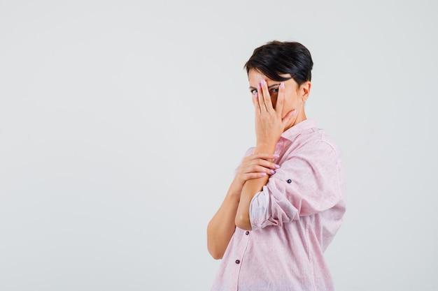 Donna in camicia rosa guardando attraverso le dita e guardando spaventata, vista frontale.