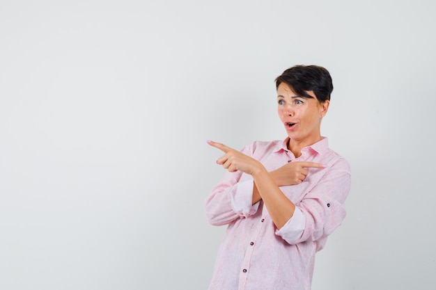 Female in pink shirt pointing at something away and looking amazed , front view.