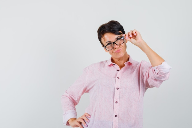 Female in pink shirt posing while looking through glasses and looking nice , front view.
