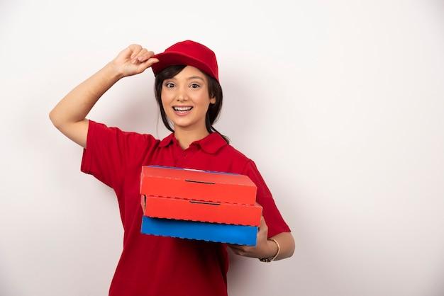 Operaio di consegna pizza femminile in piedi con tre cartoni di pizza.