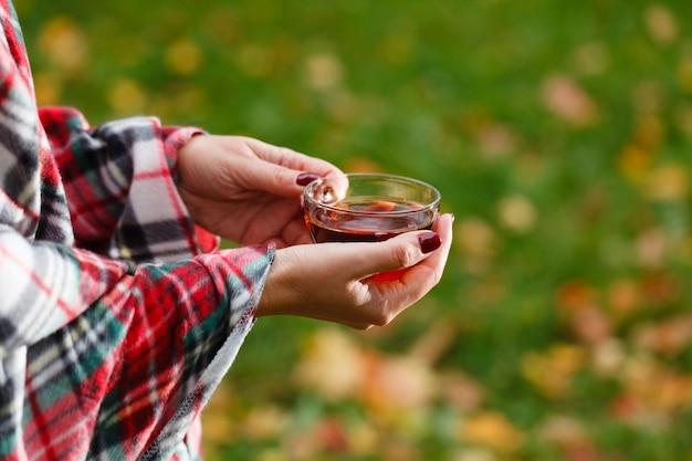 Female in plaid drink hot tea in park
