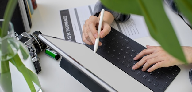 Female planning her trip on blank screen tablet with travel insurance form and other travel accessories