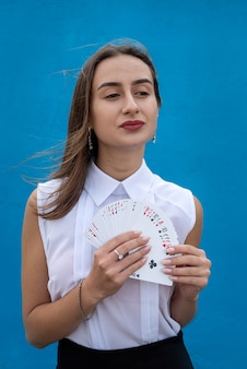 Female player holding poker cards isolated on blue background. game