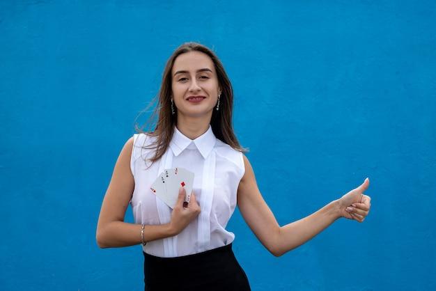 파란색 배경에 고립 된 포커 카드를 들고 여성 선수. 게임