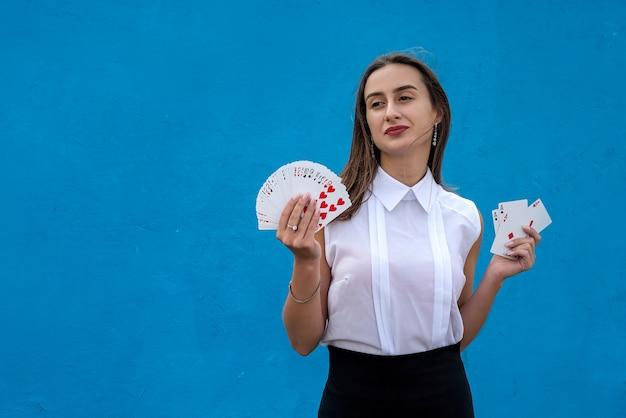 파란색 배경에 고립 된 포커 카드를 들고 여성 선수. 경기