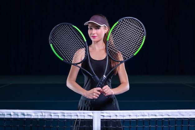 Игрок, держащий теннисные ракетки сеткой