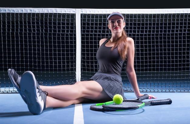 Игрок с теннисными ракетками и мячом, сидя у сетки