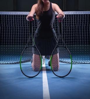Игрок с теннисными ракетками, сидя у сетки