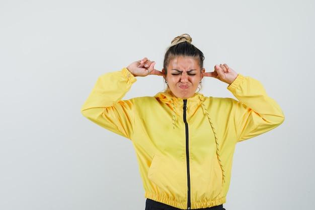 여성 스포츠 정장에 손가락으로 귀를 연결하고 짜증이 나는 전면보기를 찾고 있습니다.