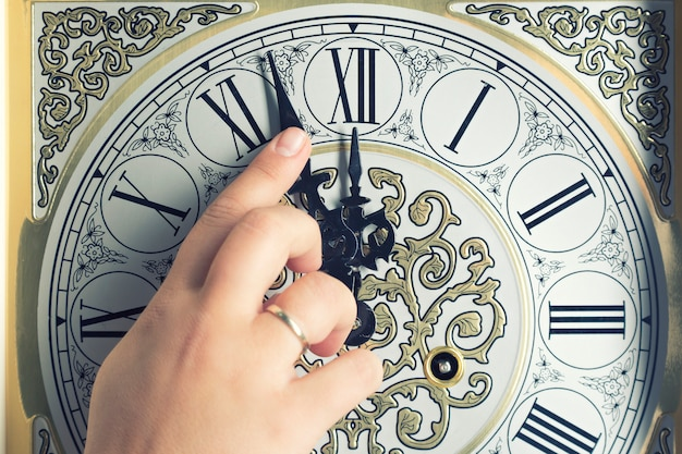 Female pointed finger on old vintage clock showing five to midnight.