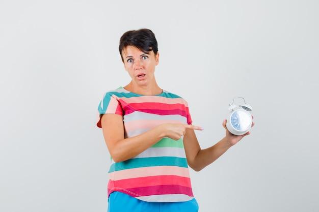 Donna che indica alla sveglia in maglietta a righe, pantaloni e sguardo perplesso. vista frontale.