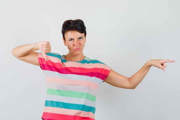 Donna che indica da parte, mostrando il pollice verso il basso in maglietta a righe e guardando dispiaciuto, vista frontale.