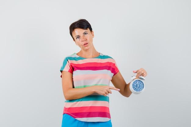 Женщина указывает на будильник в полосатой футболке, штанах и выглядит уверенно. передний план.