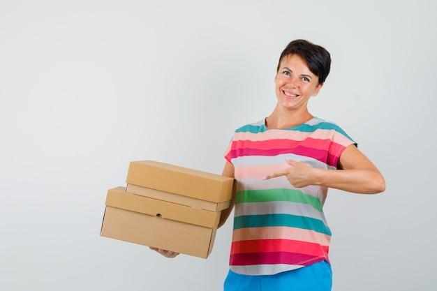 ストライプのtシャツ、ズボンの段ボール箱を指差して陽気に見える女性。正面図。